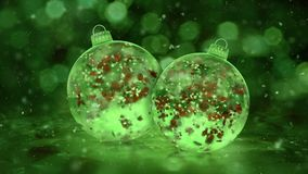 Two Rotating Christmas Green Ice Glass Baubles snow red petals background loop
