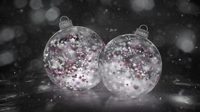 Two Rotating Christmas White Ice Baubles snow colorful petals background loop