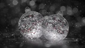 Two Rotating Christmas White Ice Glass Baubles snow red balls background loop
