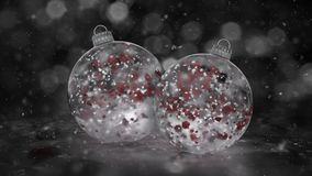 Two Rotating Christmas White Ice Glass Baubles snow red petals background loop