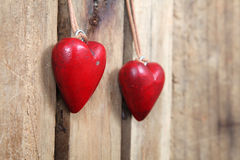 Red hearts. Two rough wooden red hearts on a wooden background royalty free stock photo