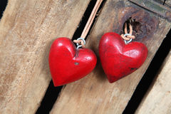 Red hearts. Two rough wooden red hearts on a wooden background royalty free stock images