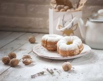 Two round cupcakes on a white plate. Behind it is a bag of nuts and a white vintage teapot royalty free stock images