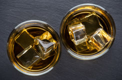 Two round glasses aged whiskey with ice Royalty Free Stock Image