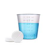 Two round medical pills with water in graded volume isolated on Royalty Free Stock Image