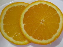 Two round pieces of an orange. Two round slices of orange close-up on white background stock images