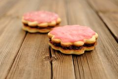 Two round sand cakes decorated with pink icing and jam on rustic Royalty Free Stock Photo