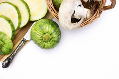 Two round zucchini cut in slices and wicker basket with vegetables Stock Photos