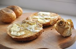 Two Rounded Slices of Bread with Butter, two baked potatoes and a dry white rose on a Wooden Chopboard royalty free stock photography