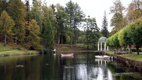 Two row boats and a lake pavilion. Found at the side of the lake and rows of trees in one side stock footage