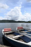Two row boats at pier on lake Stock Image