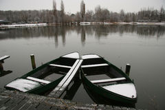 Two rowing boats covered with snow in winter lake. Line of snow covered trees reflecting in water at opposing side Royalty Free Stock Image