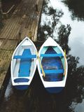 Two rowing boats by jetty on lake Stock Photo