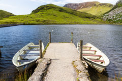 Two rowing boats by jetty, Snowdonia. Royalty Free Stock Image