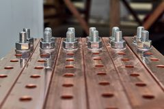 Two rows of bolts with washers and nuts fixed in busbars. Metal bolts with nuts and washers are fixed in the holes. Busbars at high current and high voltage Royalty Free Stock Photo