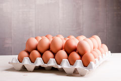 Two rows of brown eggs in a tray on a light wooden table side vi Stock Photos