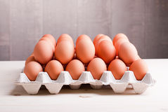 Two rows of brown eggs in a tray on a light wooden table side vi Royalty Free Stock Photography