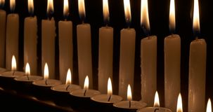 Two rows of candles on black background. Two rows of white candles. Dim candlelight in a dark room stock video footage