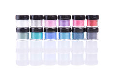 Two rows of loose eye shadows in plastic jars Royalty Free Stock Image