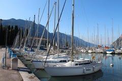 Two rows of sailboats, dock at Lake Riva, Italy. Two rows of sailboats at Lake Riva, Italy, under the mountains Royalty Free Stock Photography