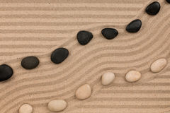 Two rows of stones lying on the sand, with space for text. Royalty Free Stock Photography
