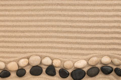 Two rows of stones lying on the wavy sand, with space for text. Royalty Free Stock Photography
