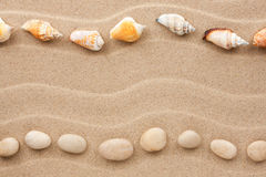Two rows of stones and shells on the sand Stock Photos