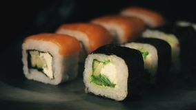 Two rows of sushi in a cloud of smoke, rolls on a slate board, food background, Japanese cuisine stock footage