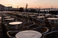 Venedig. Tische stehen in Reihen auf dem Markusplatz in Venedig. Die frische Morgenstimmung taucht die Szenerie in ein goldenes Licht royalty free stock photos