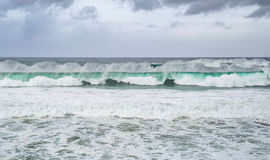 Two rows of turquoise sea waves, water foam and dramatic clouds stock image
