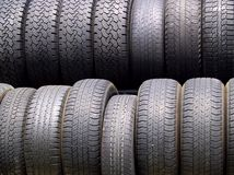 Two rows of used tires in diffused light. With upper row in sharp, shallow focus Royalty Free Stock Images