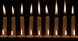 Two rows of white candles. Two horizontal rows of white candles with tall flames on black background stock footage