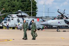Two Royal Air Force Pilots walking across the tarmac at RAF Waddington with aircraft sitting in the background. royalty free stock photography
