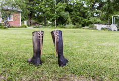 Two rubber boots on a green lawn near red house in farm. Close-up image of rubber boots on a green grass near red house in a farm Stock Image