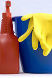 Two rubber gloves in a blue and red spray bottle. Two rubber gloves in a blue bucket with a  red spray bottle Stock Image