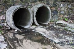 Two run-off pipes discharging water Stock Photo