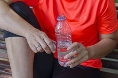 Two runner women rest with water bottle on a bench. Stock Images
