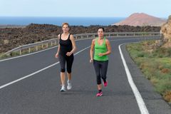 Two Runner women running on mountain road Stock Image