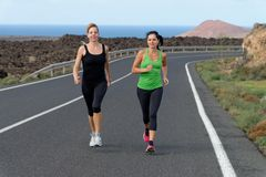 Two Runner women running on mountain road Stock Photos