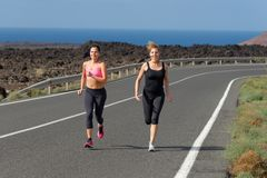 Two Runner women running on mountain road Stock Photography