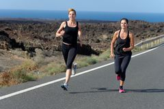Two Runner women running on mountain road Royalty Free Stock Image