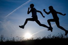 Two runners. Two men make jog in the field on a sky background by at sunset Stock Images