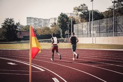 Two runners actively enter the turn. Runs through the stadium Stock Images