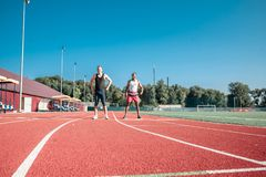 Two runners against the blue sky in the stadium warm up. Two runners against the blue sky at the stadium are warming up Royalty Free Stock Photos