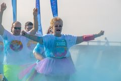 4 - 6 - 2019 - Two runners - on a senior citizen woman in a tutu and a balding man behind her - hold their arms up as they run. Through colored powder at a stock image