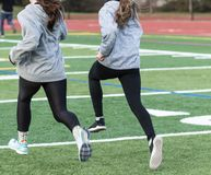 Two runners spinting on green turf field stock images
