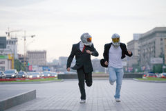 Two running businessmen with gas masks Stock Photos