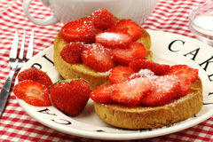 Two rusks with sugared strawberries Royalty Free Stock Photo