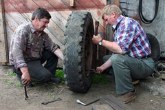 Two russian farmers repair wheel in the territory farm garage. Stock Photos