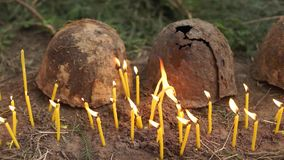 Two rusted soldier's helmet. Surrounded by burning candles stock video footage